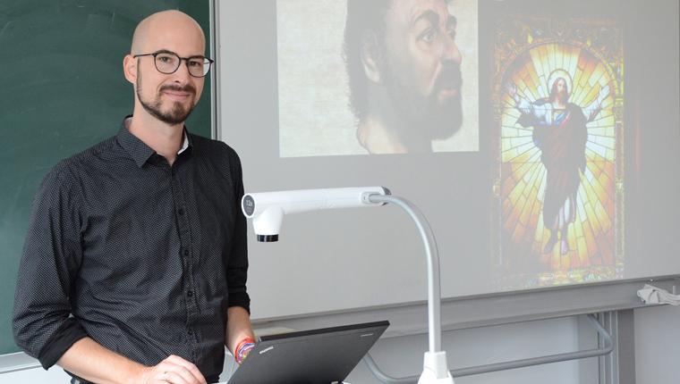 Lehrer Sebastian Kornek am Pult eines Klassenzimmers