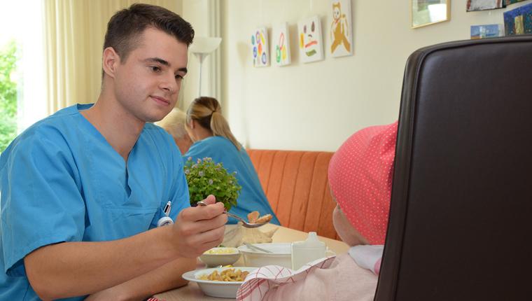Gesundheits- und Krankenpfleger Marco Kulwicki füttert ein krankes Kind