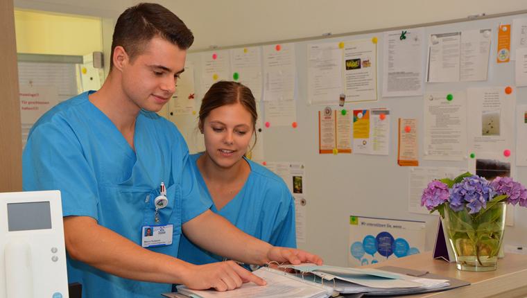 Gesundheits- und Krankenpfleger Marco Kulwicki im Gespräch mit einer Kollegin