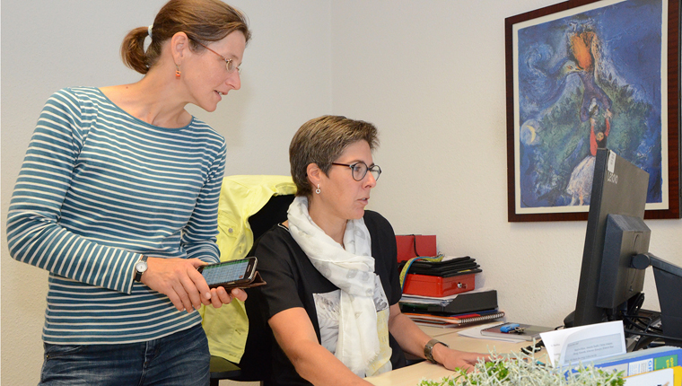 Pastoralreferentin Christiane Zirpel und Pfarrsekretärin Anja Ruffer schauen auf einen Computer-Monitor