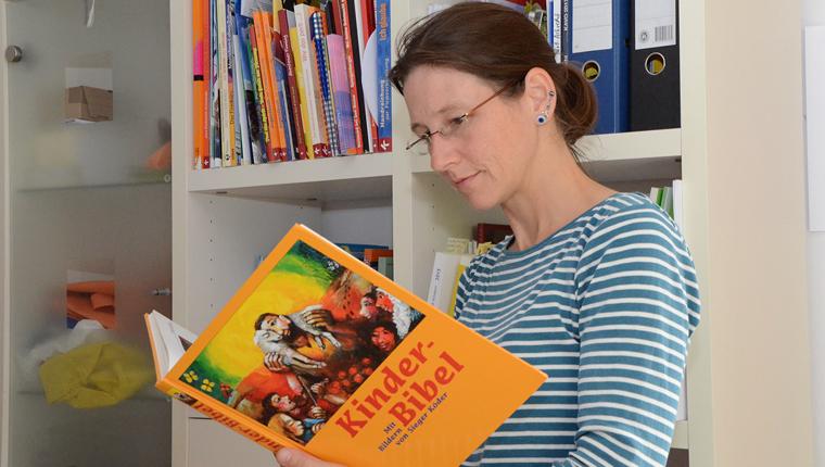 Pastoralreferentin Christiane Zirpel liest in einer Kinderbibel
